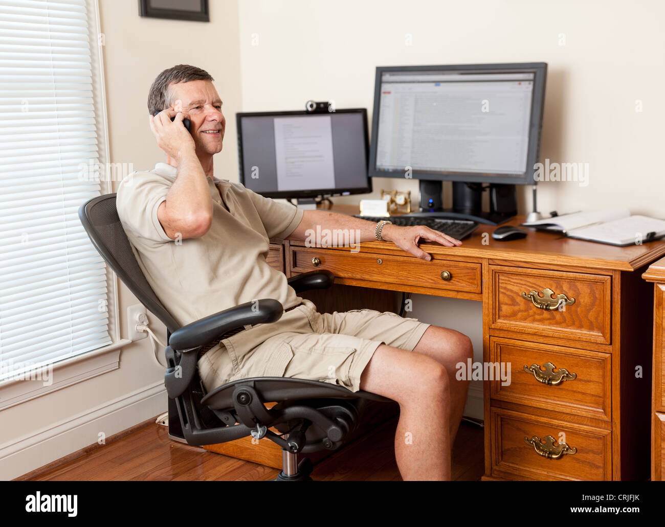 Man working from home office in shorts with desk with two monitors on the phone - Stock Image