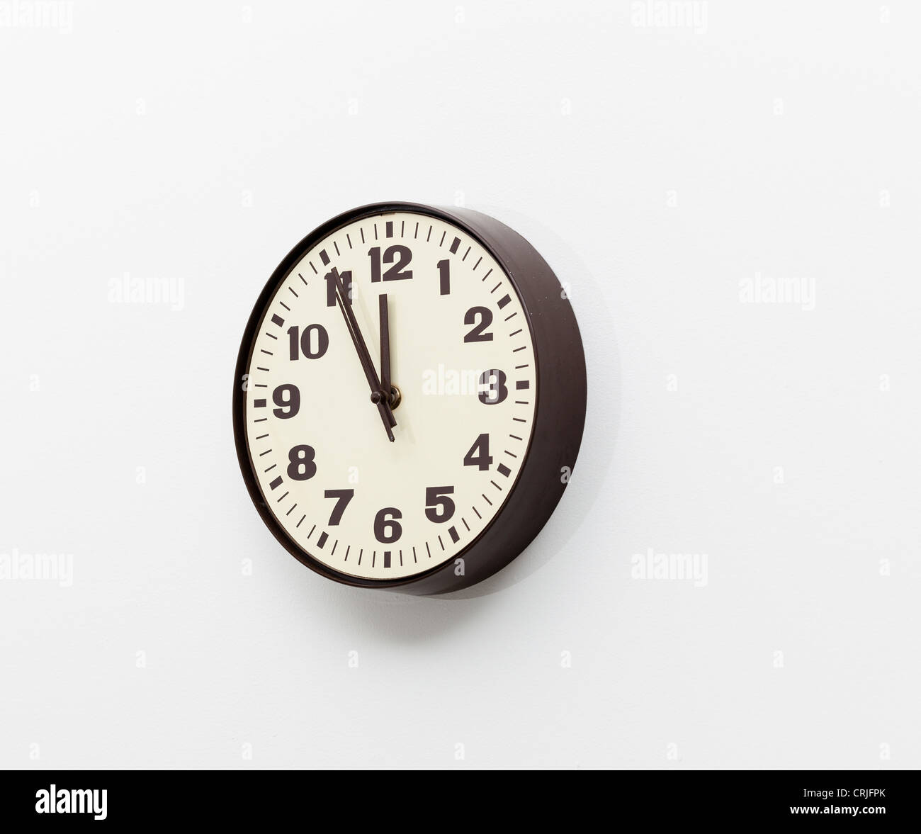 Wall clock showing five minutes to 12 o'clock - Stock Image