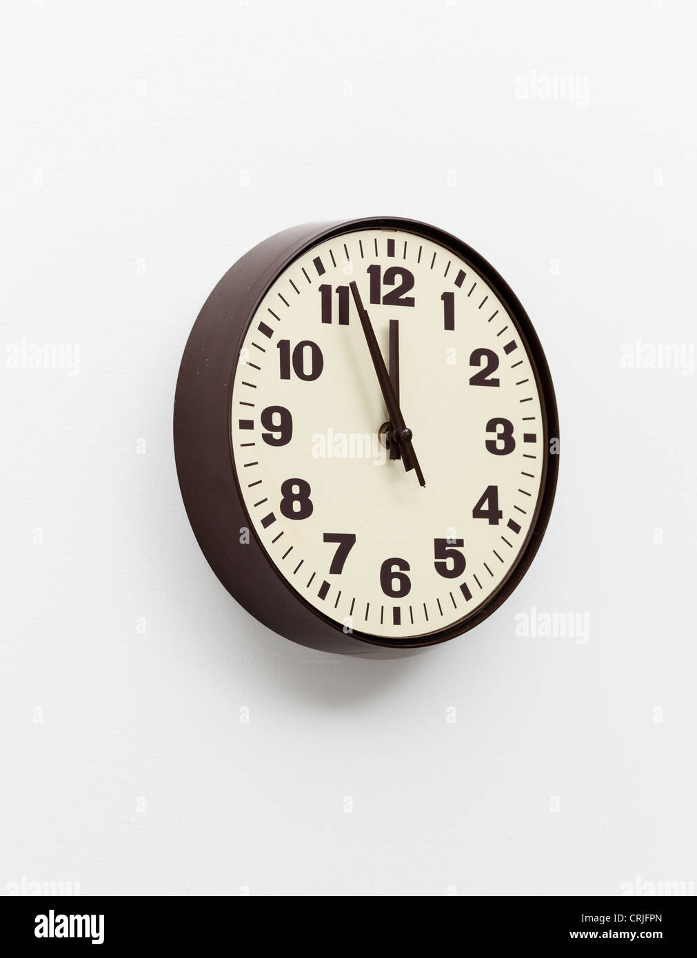 Brown simple plastic wall clock on the wall of office and concept of running out of time - Stock Image