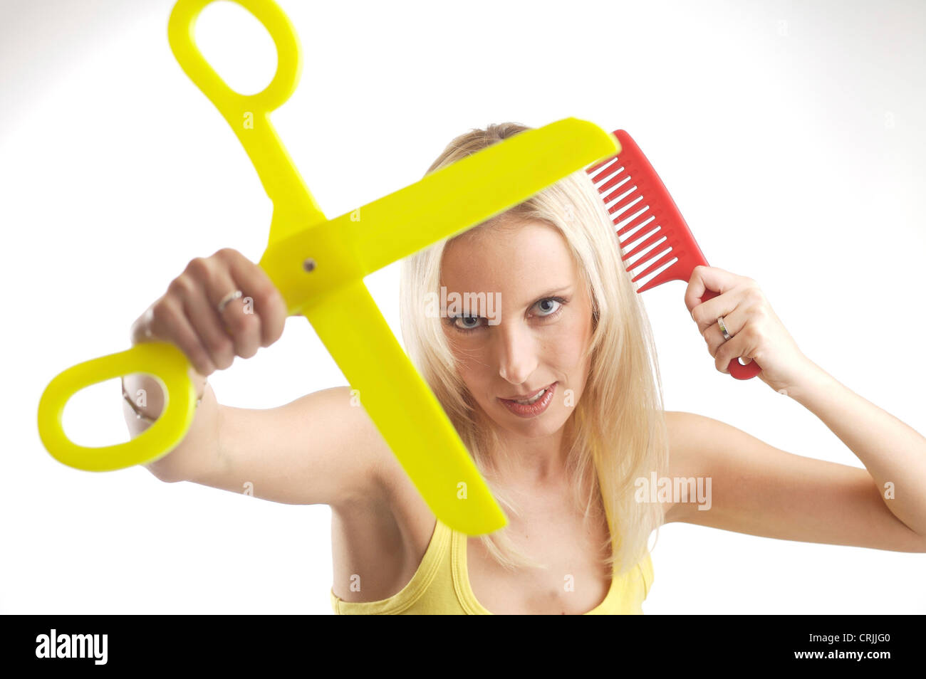 blond young woman with oversize comb and a pair of scissors - Stock Image