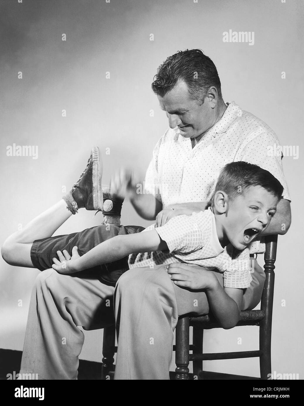 Father spanks naughty son - Stock Image