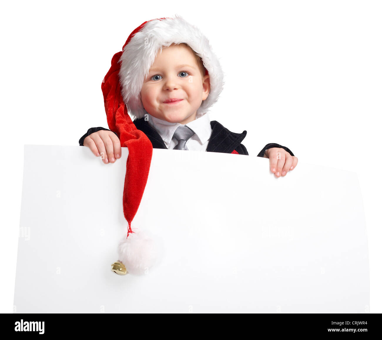 smiling young boy with a Santa cap holding an empty white panel - Stock Image