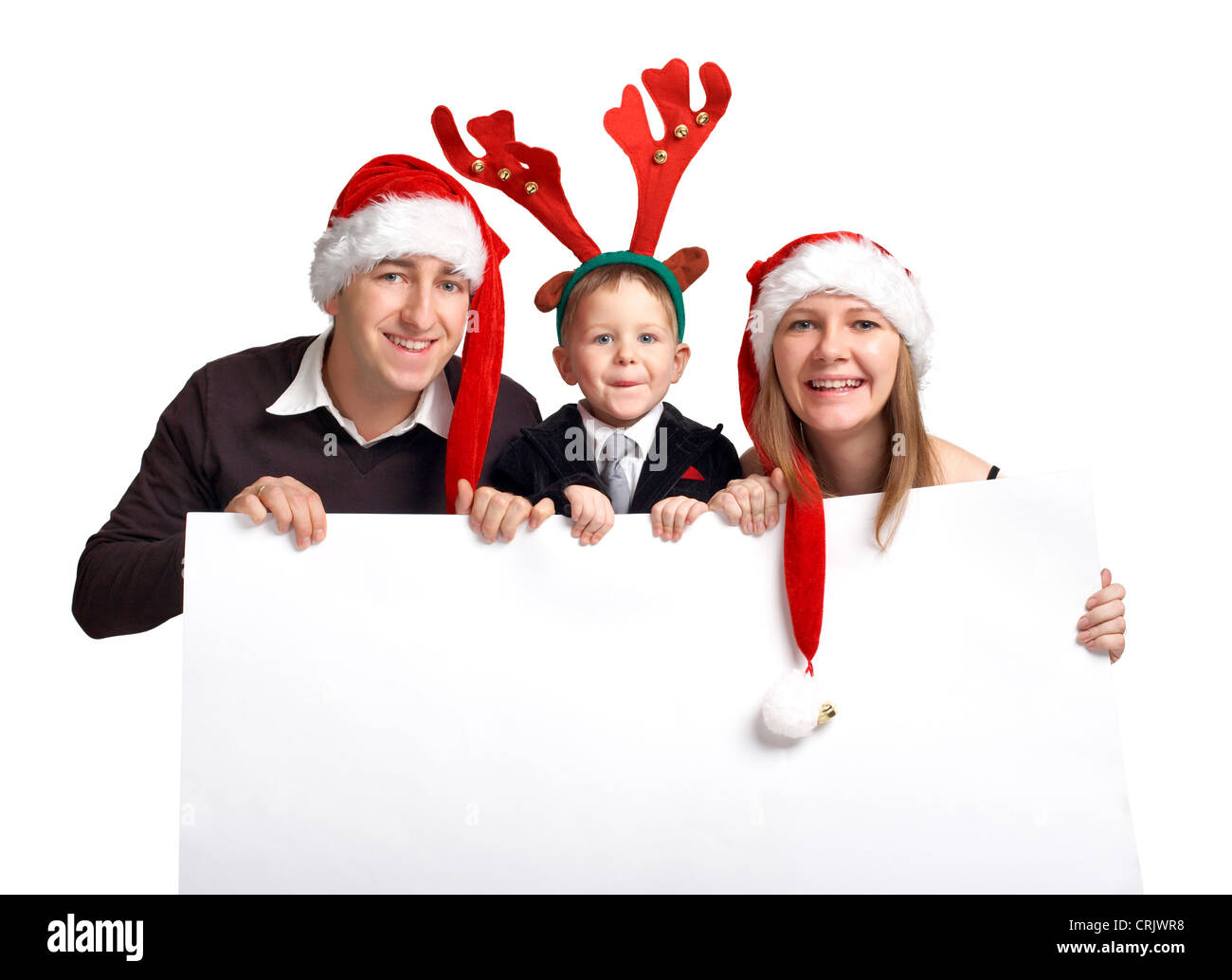 smiling young family wearing Santa caps of an elk antler holding an empty white panel - Stock Image