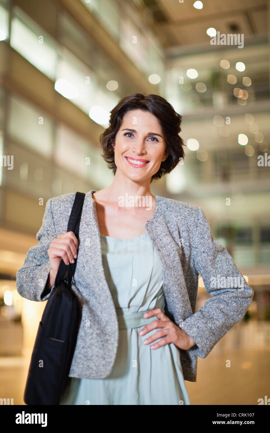 Smiling businesswoman with briefcase - Stock Image