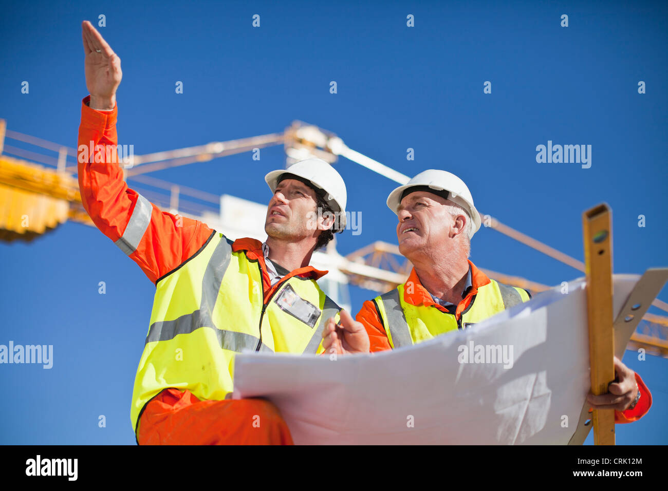 Workers reading blueprints on site - Stock Image