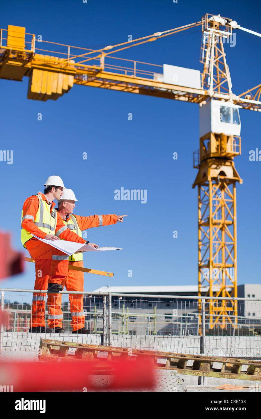 Workers reading blueprints on site Stock Photo
