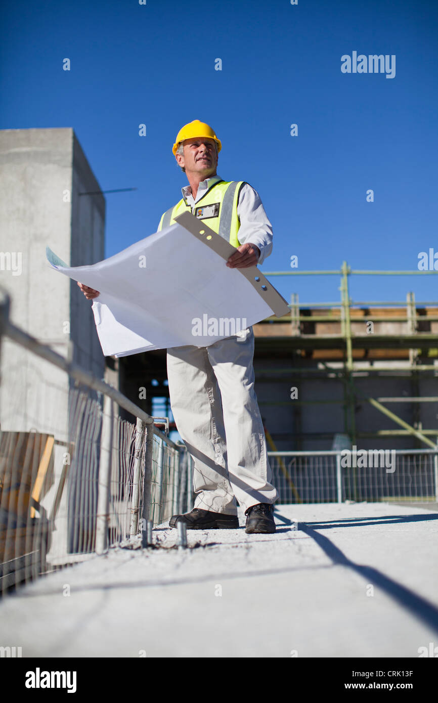 Worker reading blueprints on site - Stock Image