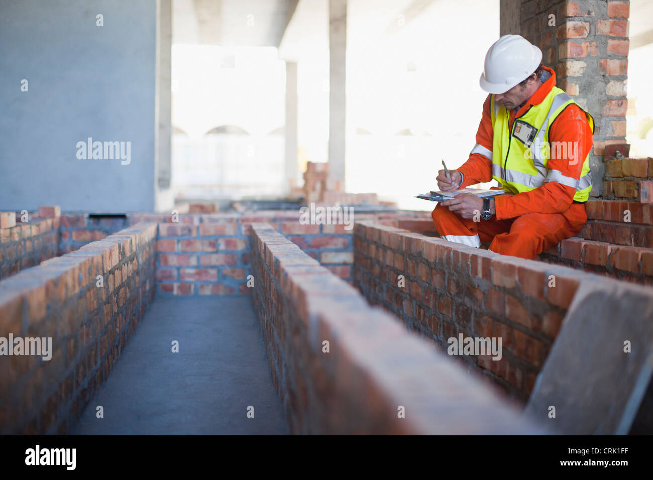 Worker writing on clipboard on site - Stock Image