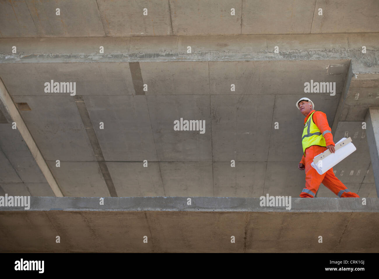 Worker carrying blueprints on site - Stock Image