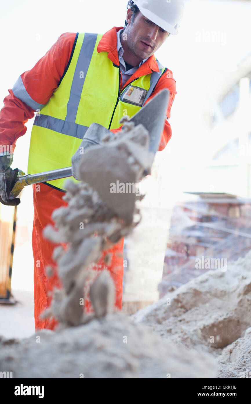 Worker shoveling concrete on site - Stock Image