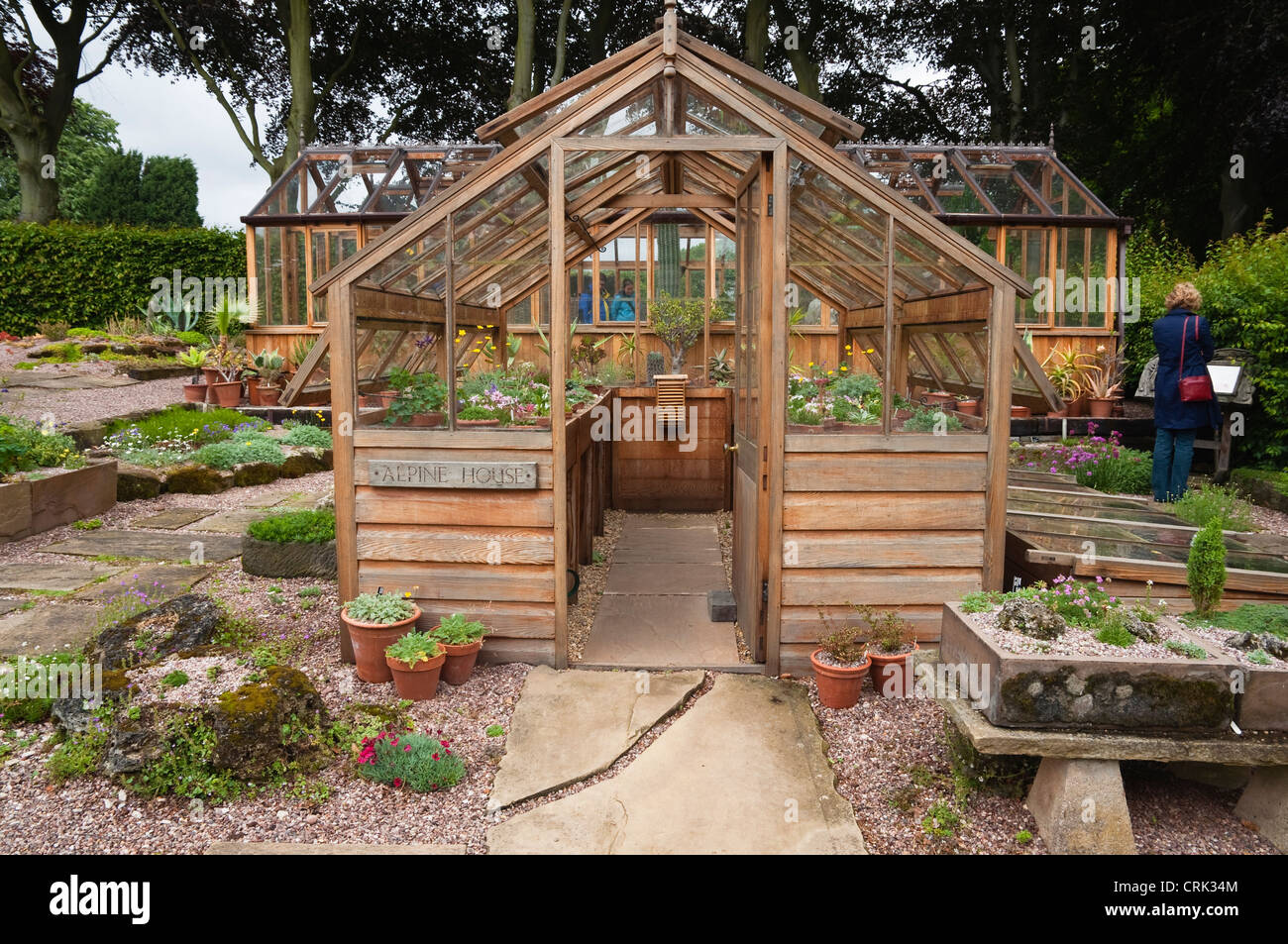 The Alpine House - a traditional wooden greenhouse, surrounded by a variety of sinks, and pots - containing alpine - Stock Image