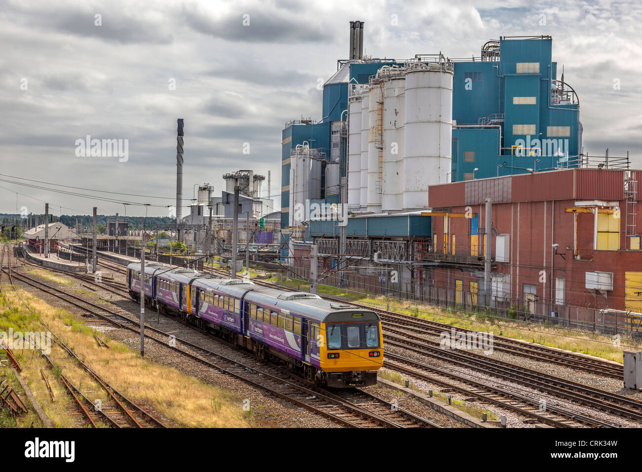 Warrington Bank Quay station with the Unilever factory behind. - Stock Image