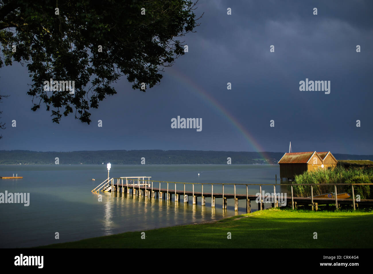 Wooden pier stretching into still water Stock Photo