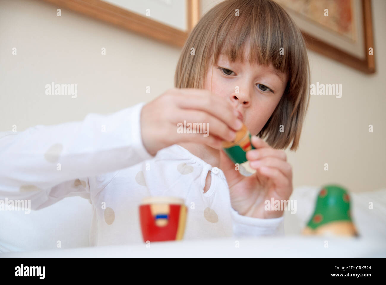 Girl playing with nesting doll - Stock Image