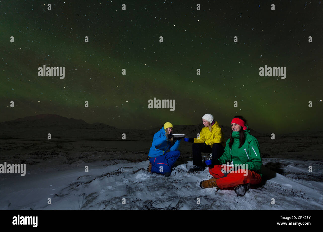 Hikers relaxing under aurora borealis - Stock Image