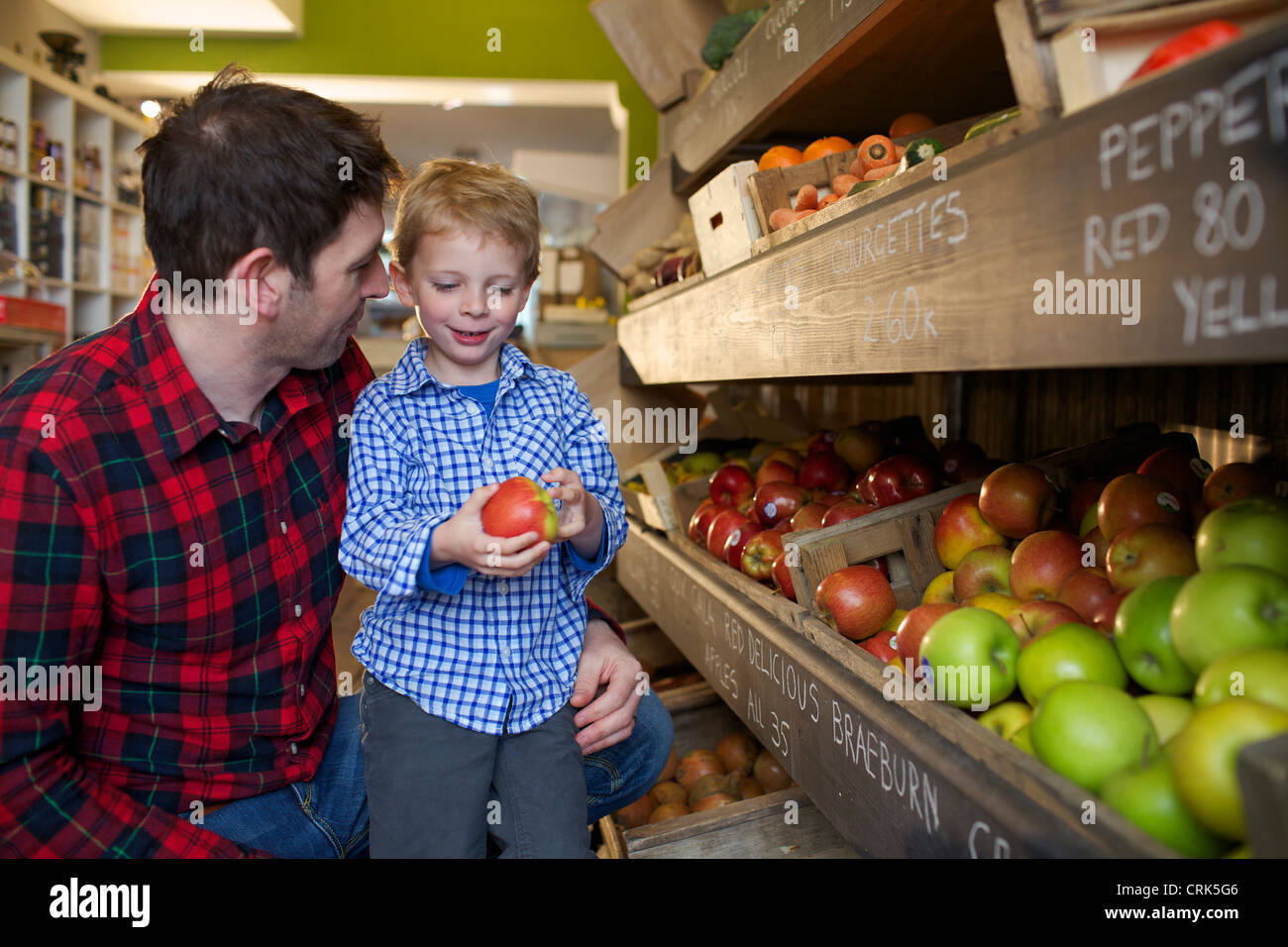 Father and son buying produce in store - Stock Image