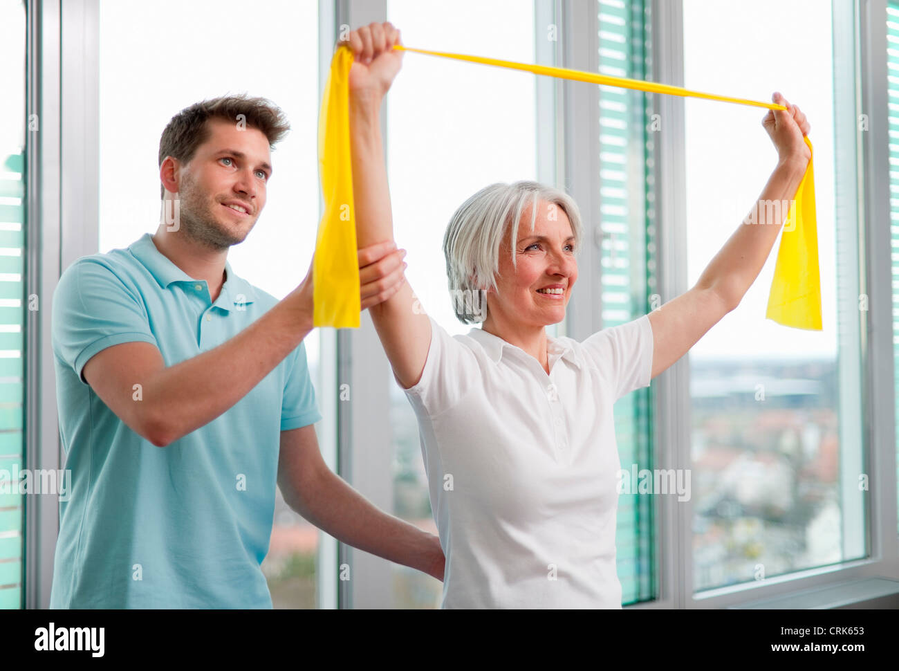 Trainer working with woman in gym Stock Photo