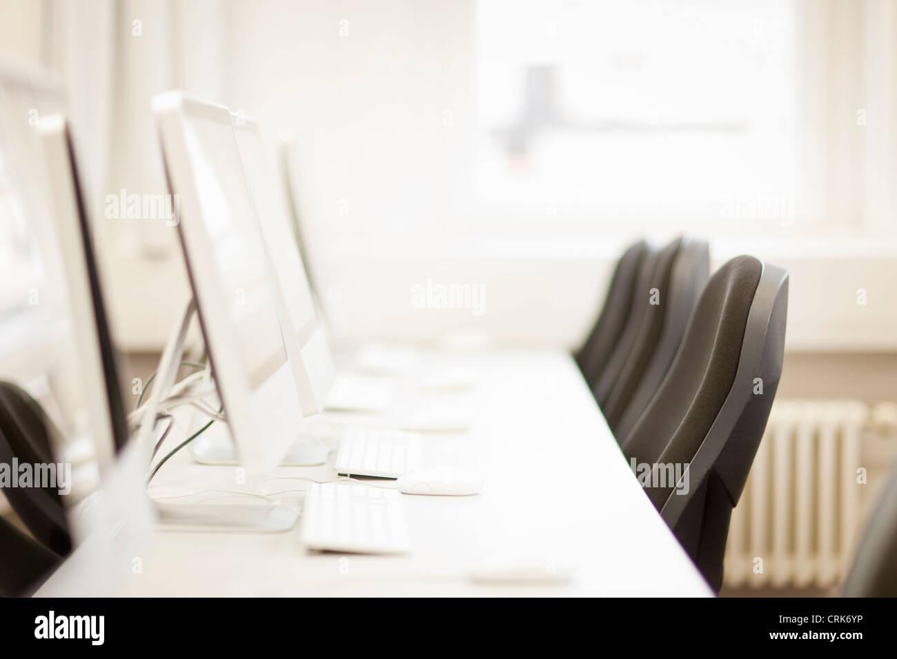 Empty computer desks in office - Stock Image