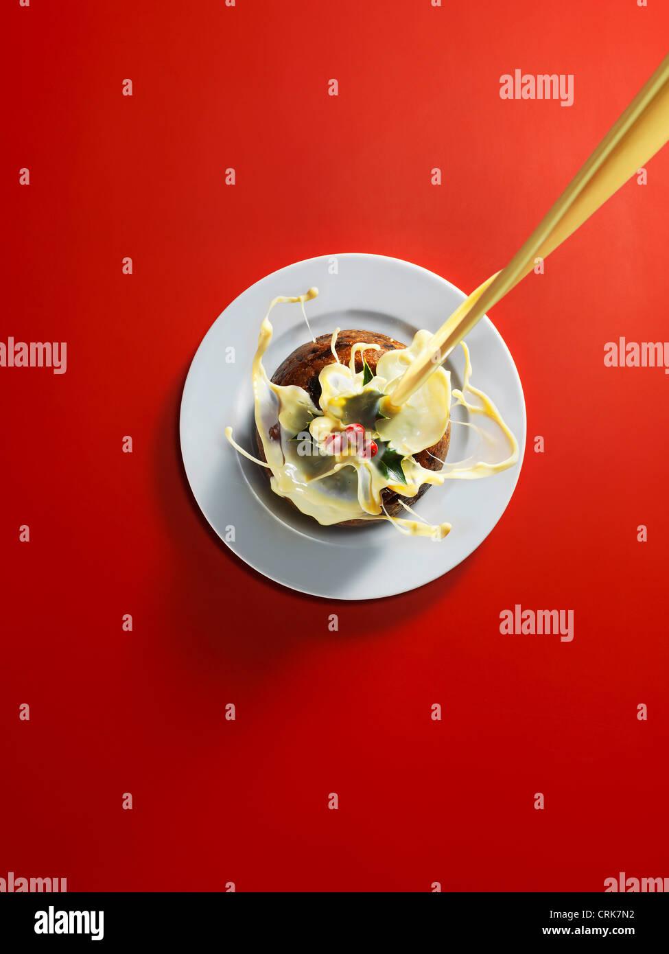 Cream pouring onto Christmas cake - Stock Image