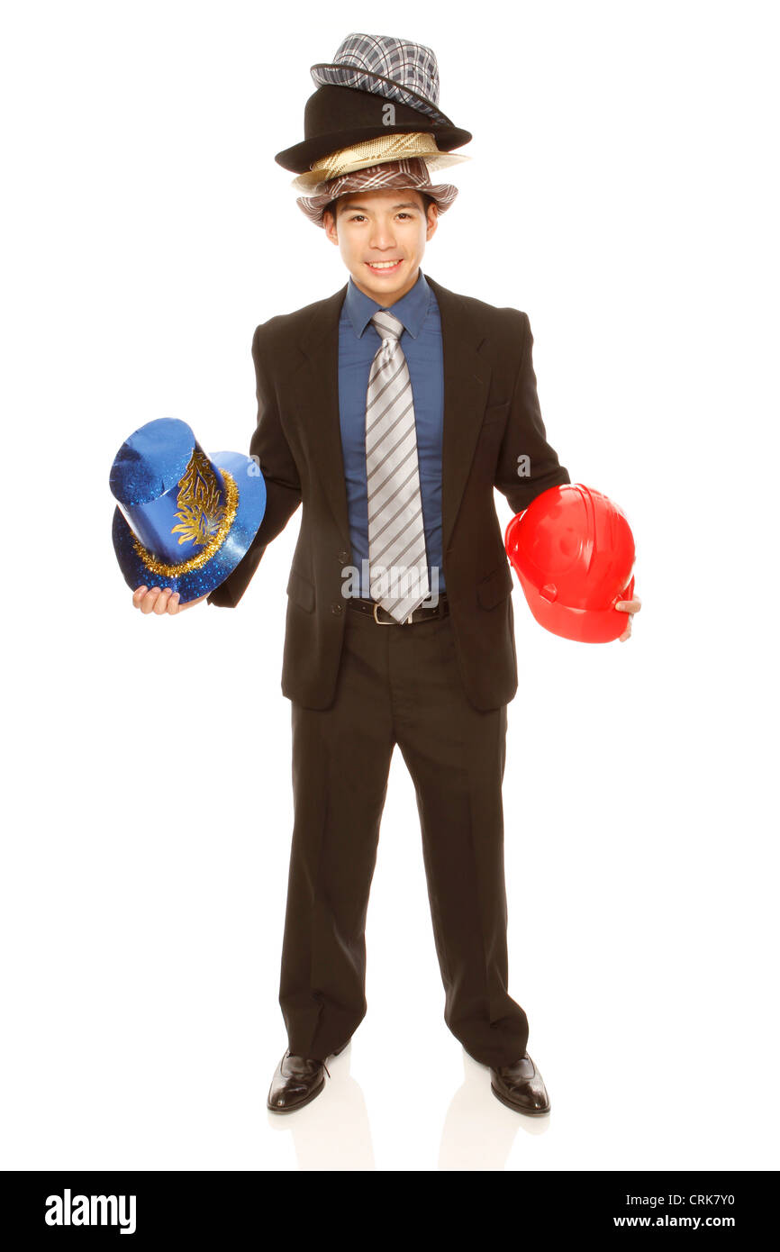 A businessman wearing and holding many hats. Iisolated on white. (For Alamy only) - Stock Image