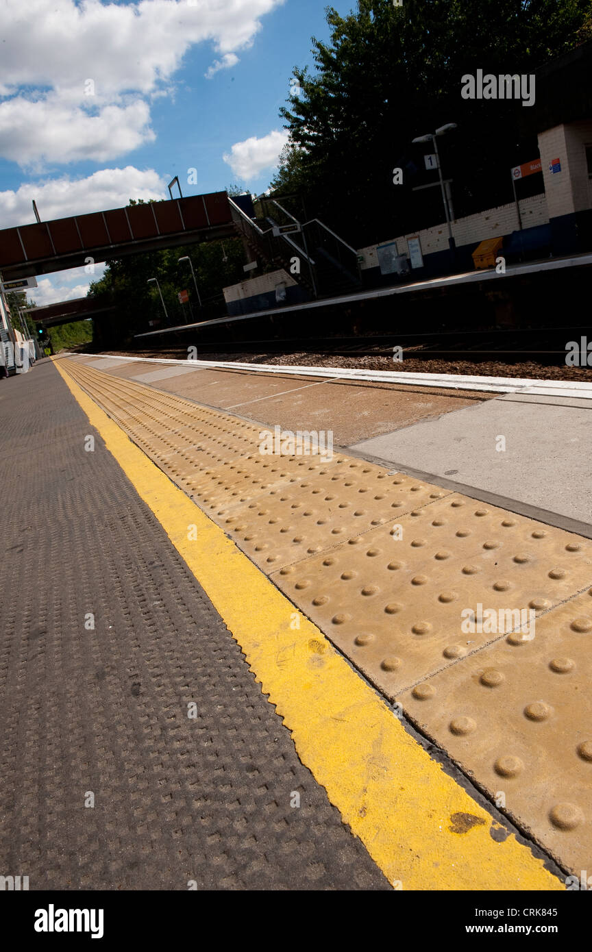 Close up of a railway station platform in England showing the yellow line that passengers should stand behind. - Stock Image