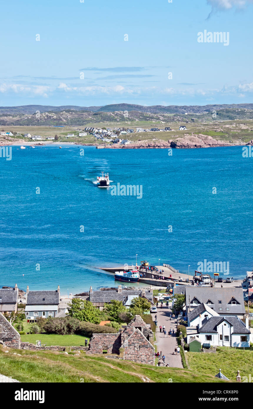 A view across Iona Sound to Mull in Scotland with town Baile Mor in the foreground and Calmac ferry Loch Buie approaching. - Stock Image