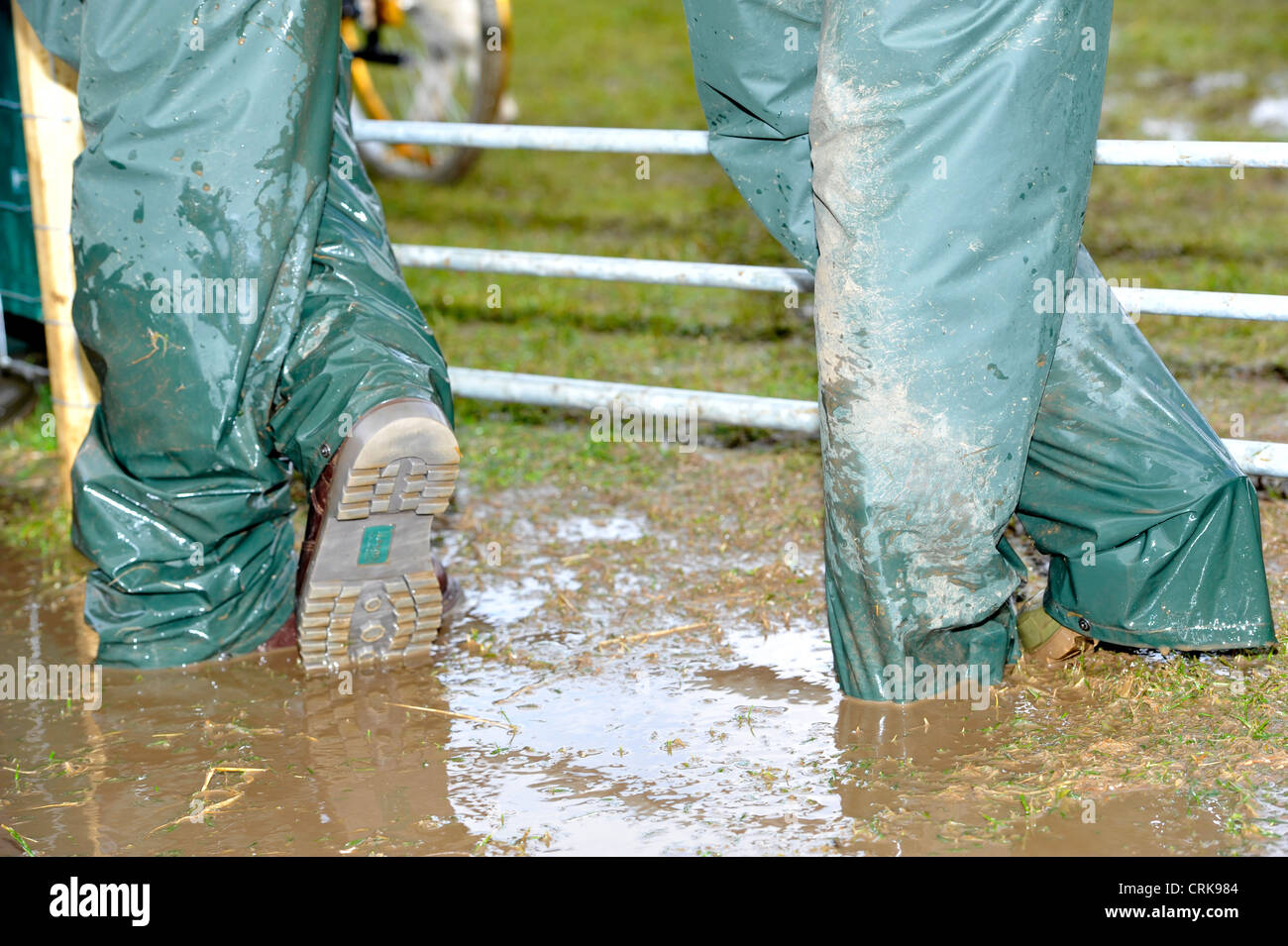 Farmers Wearing Wellington Boots And Waterproofs Standing