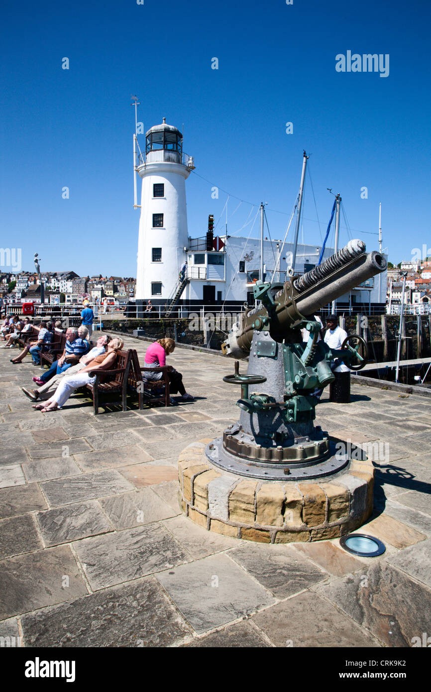 1914 Vickers Pettern 13 PDR Gun and the Lighthouse Scarborough North Yorkshire England - Stock Image