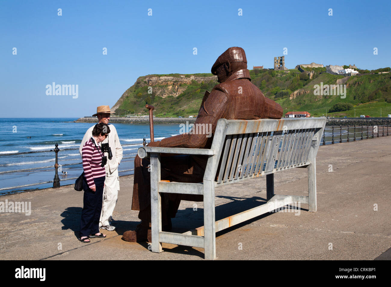 Ray Lonsdale Sculpture of a Man on a Bench in North Bay Scarborough North Yorkshire England - Stock Image