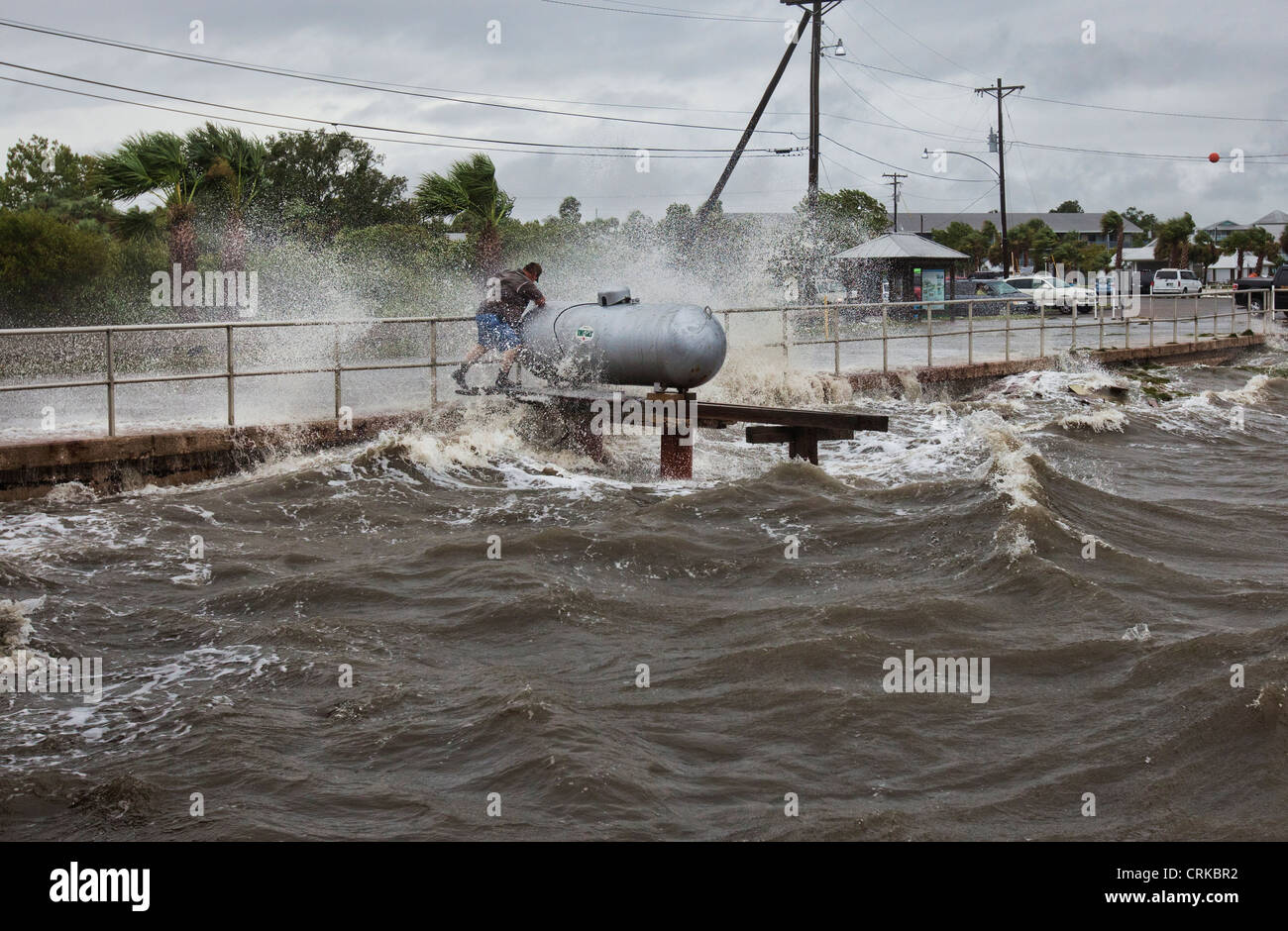 Cedar Key Water Works director climbs out onto a propane deck to shut off the valve during Tropical Storm Debby - Stock Image