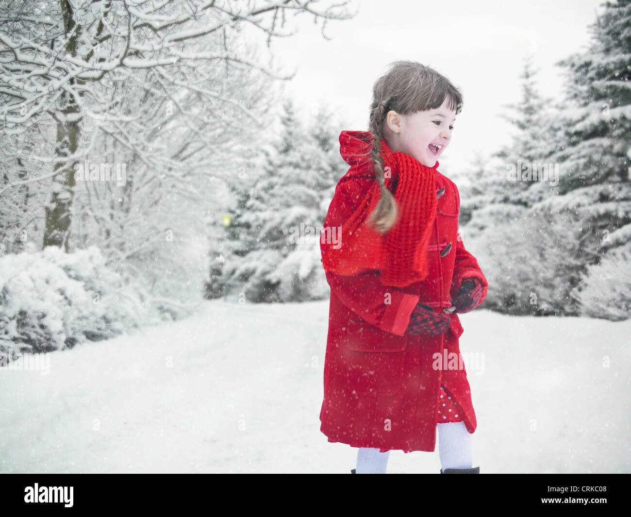 Smiling girl playing in snow - Stock Image