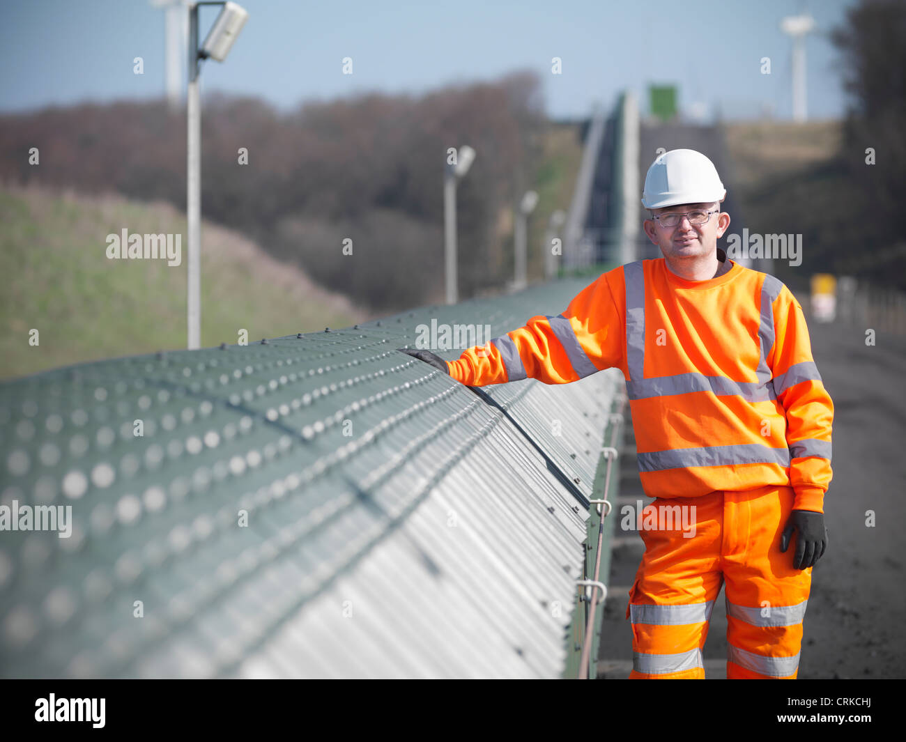 Worker by conveyor at coal mine - Stock Image