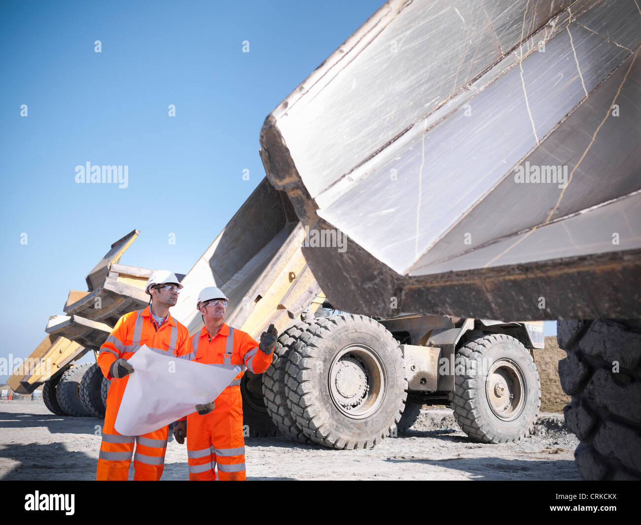Workers reading blueprints at coal mine Stock Photo