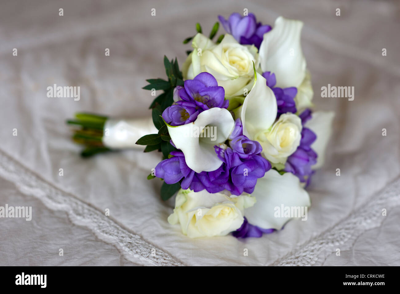 wedding bouquet of freesia, lilies and roses in white and purple - Stock Image