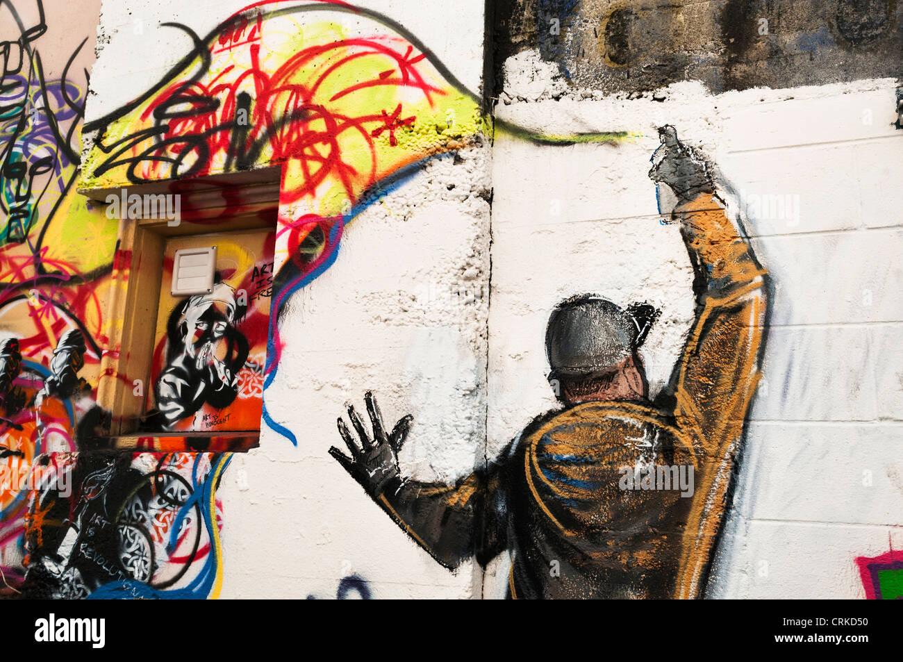 Graffiti of graffiti artist spray painting a wall in an alley in downtown aberdeen washington