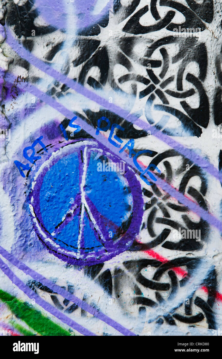 Abstract graffiti with peace sign spray painted on an alley wall in downtown Aberdeen, Washington. - Stock Image