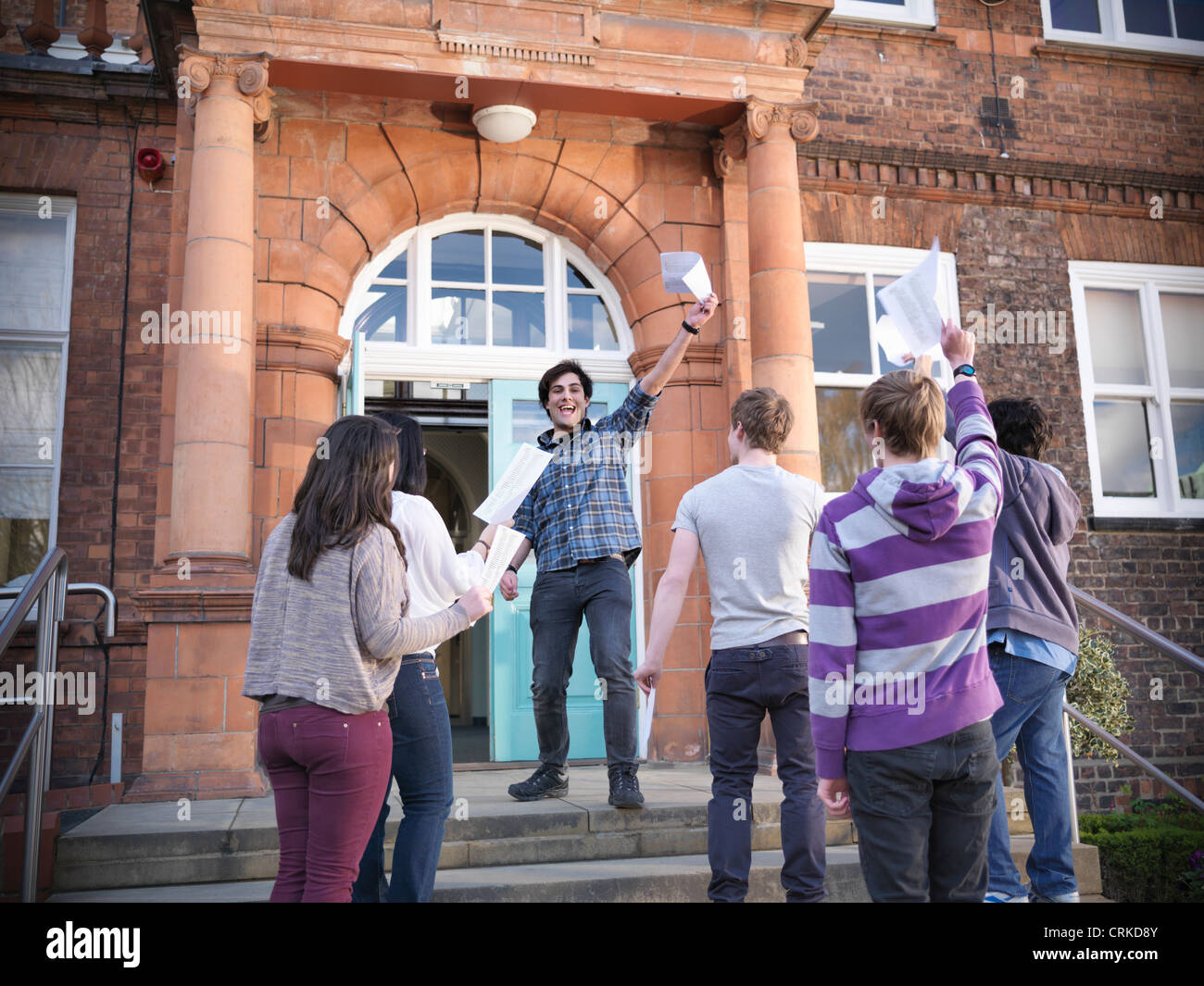 Students with grades cheering at school - Stock Image