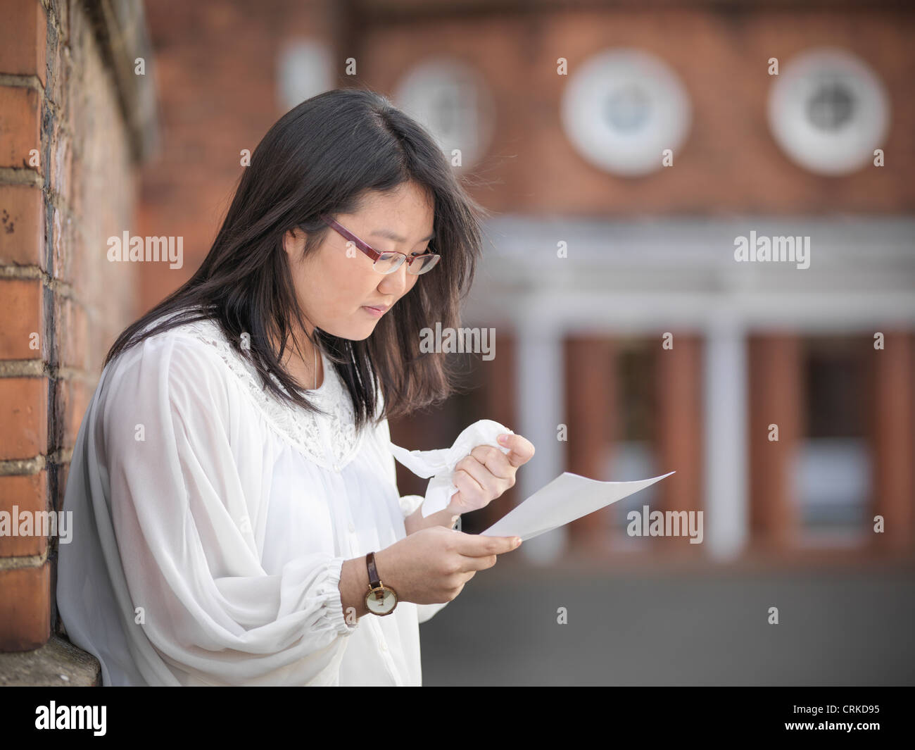 Crying student reading grades at school - Stock Image