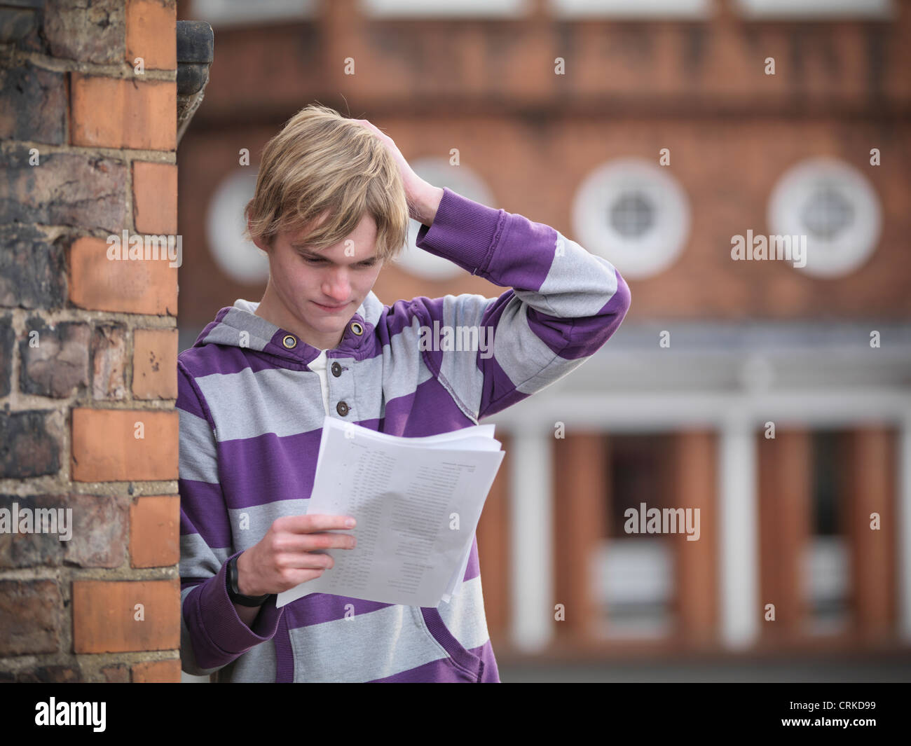 Upset student reading grades at school - Stock Image