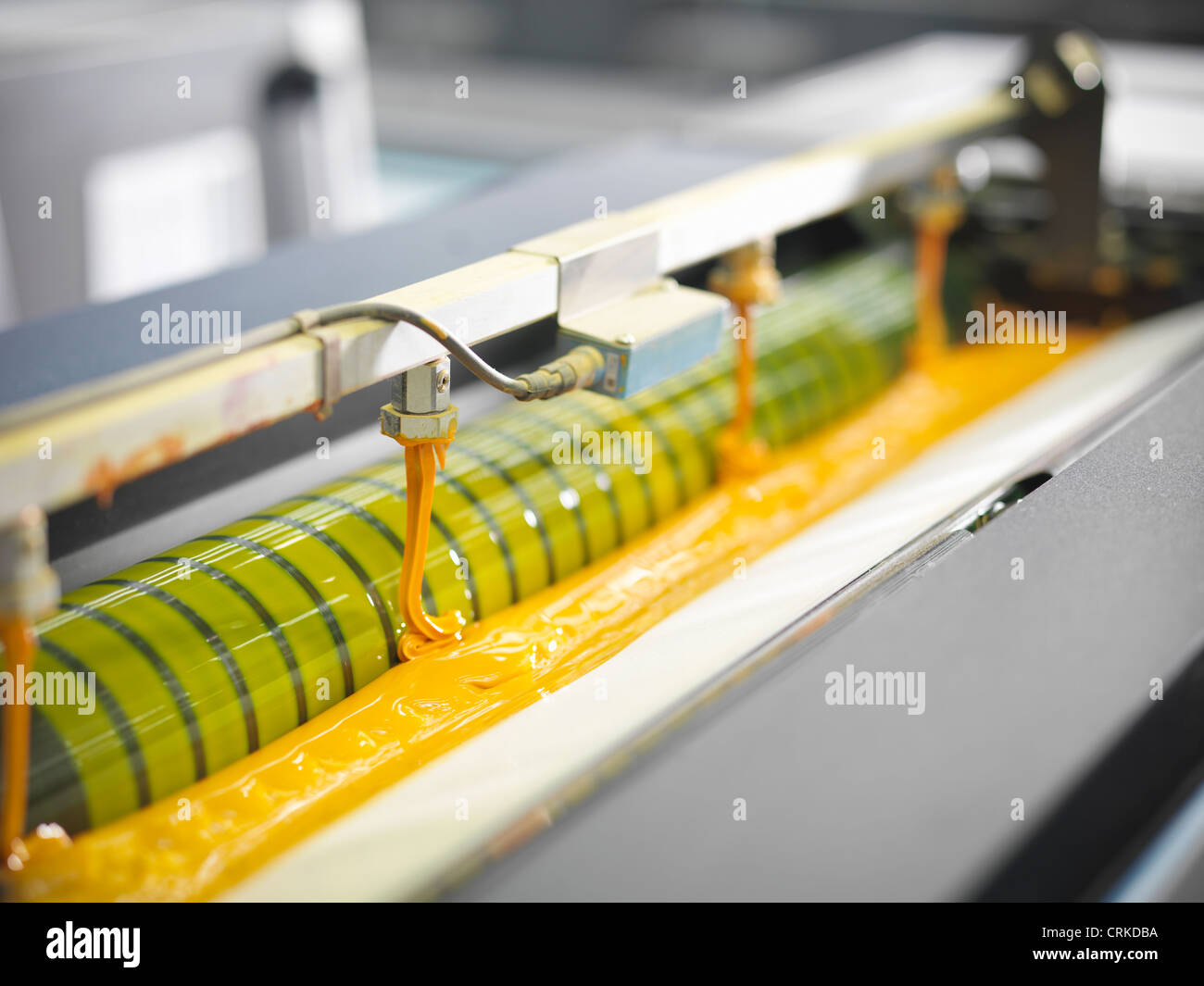 Close up of yellow ink in printing press - Stock Image