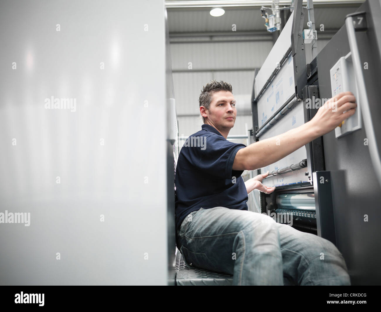 Worker changing plates on printing press Stock Photo