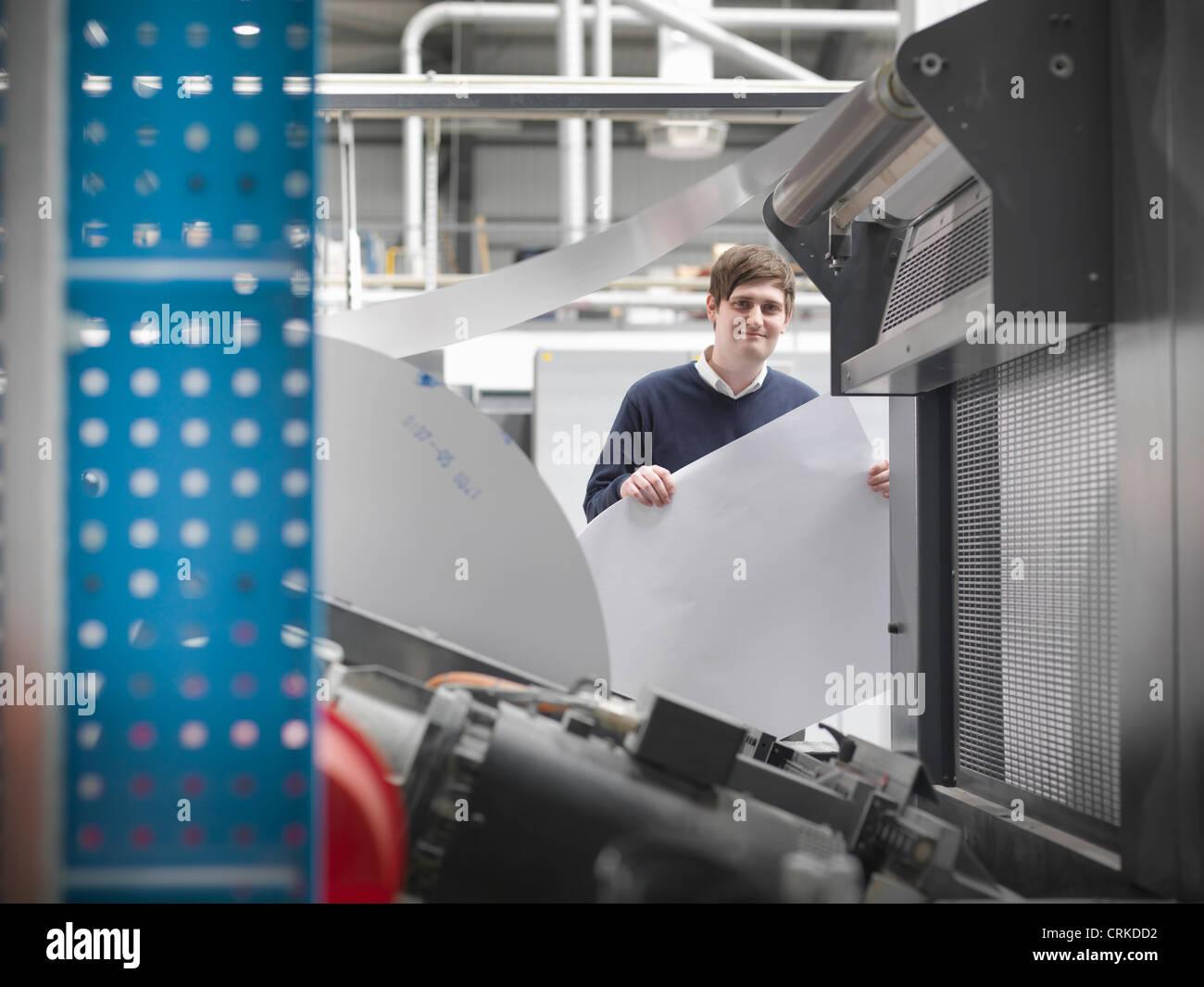 Printer holding paper at press - Stock Image