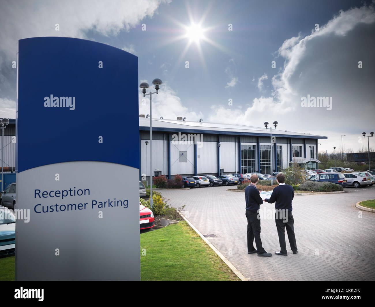 Businessmen standing in parking lot - Stock Image