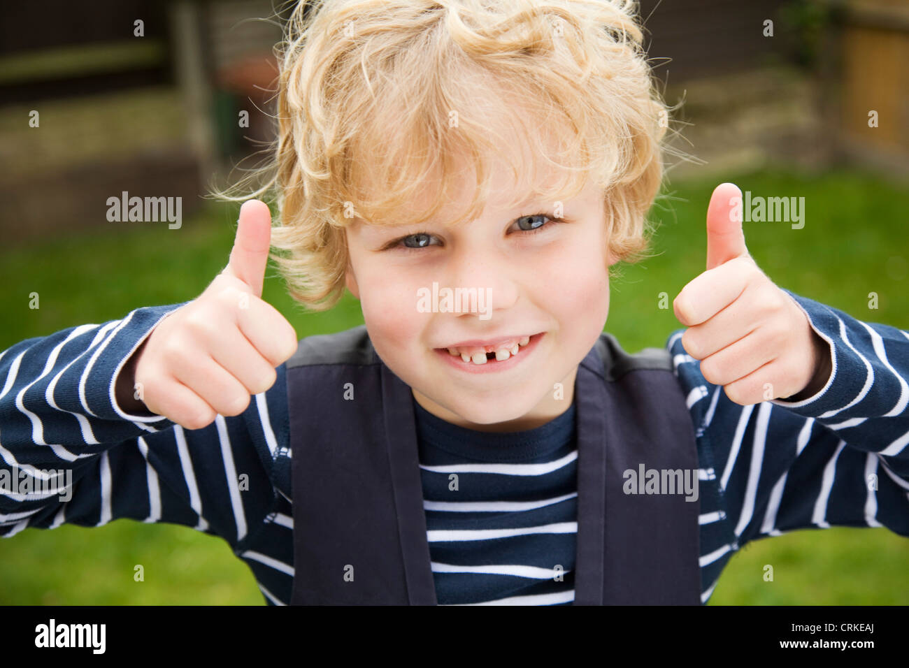 Smiling boy giving thumbs-up outdoors - Stock Image