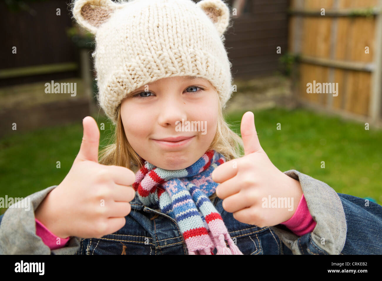 Smiling girl giving thumbs-up outdoors - Stock Image