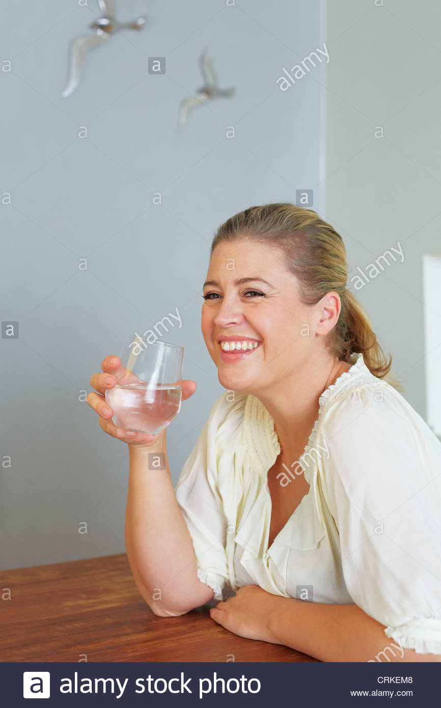 Woman having glass of water at table - Stock Image