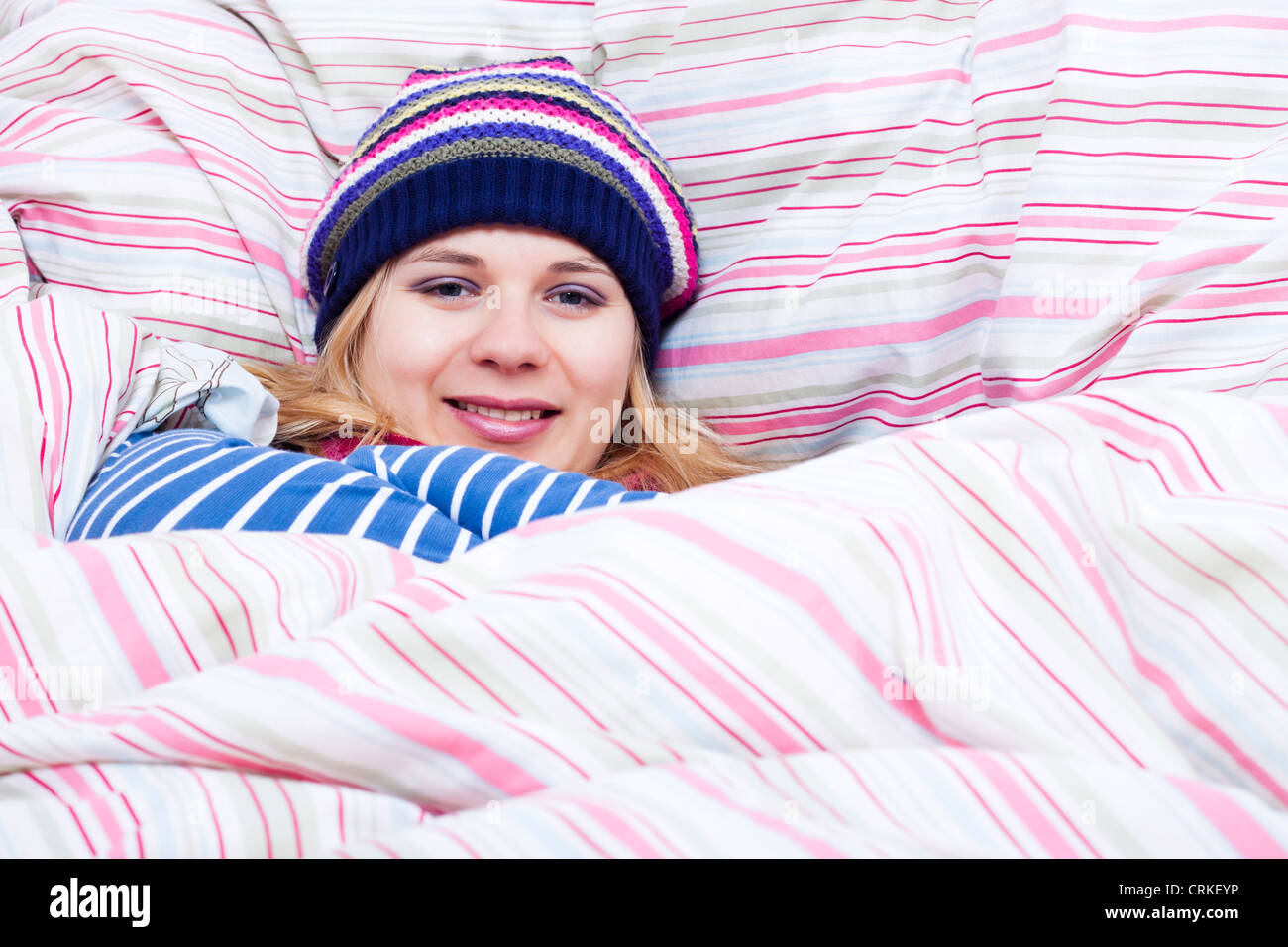 Young happy smiling woman in winter hat wrapped in duvet. - Stock Image