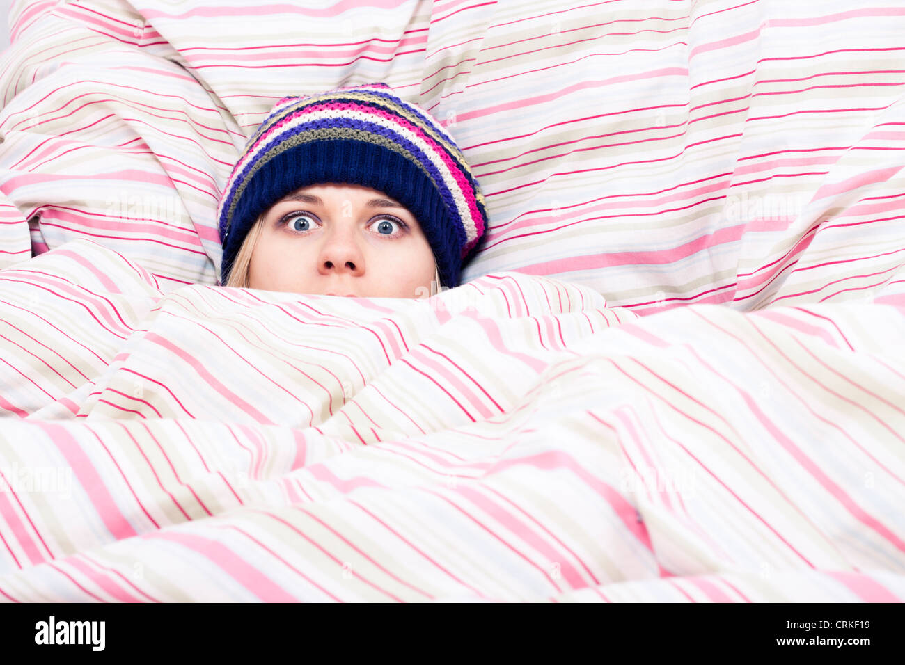 Scared woman in winter hat hiding wrapped in duvet. - Stock Image