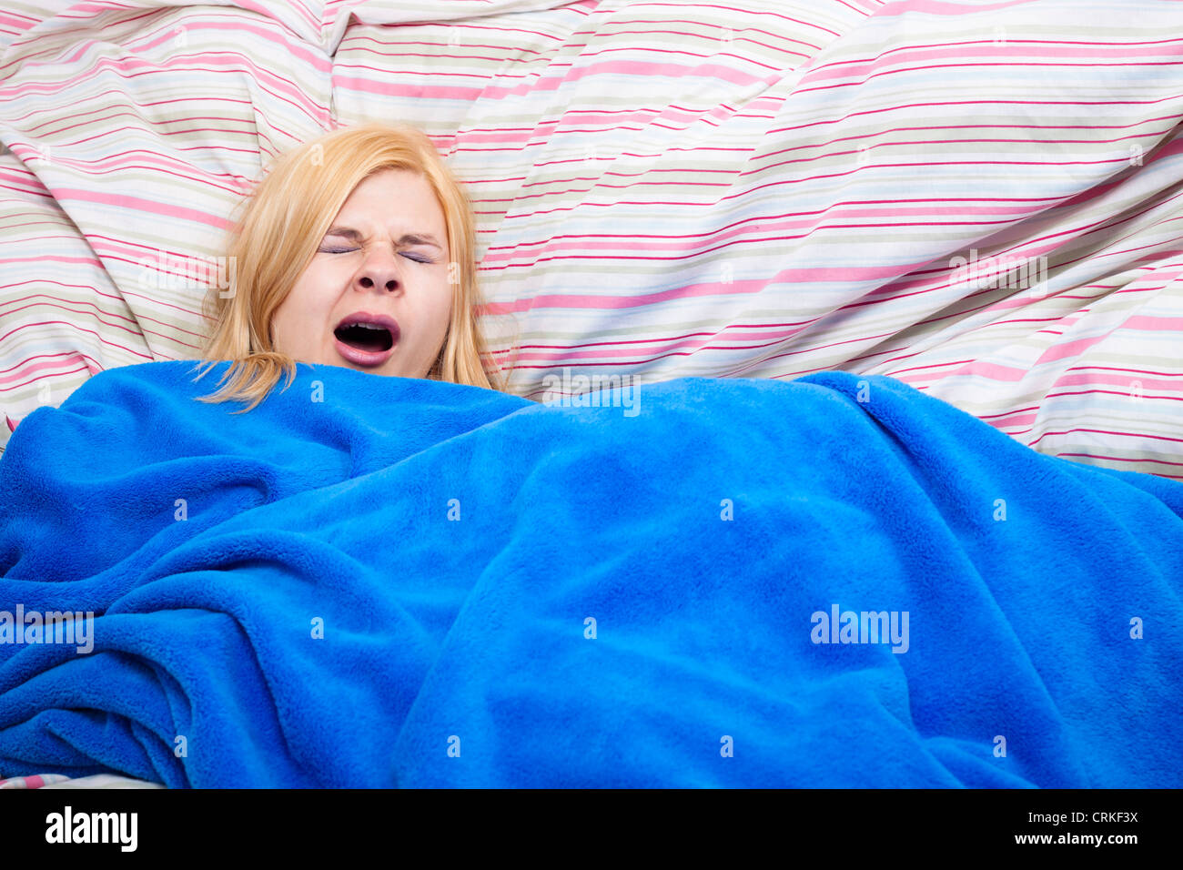 Sleepy woman yawning wrapped in a duvet. - Stock Image