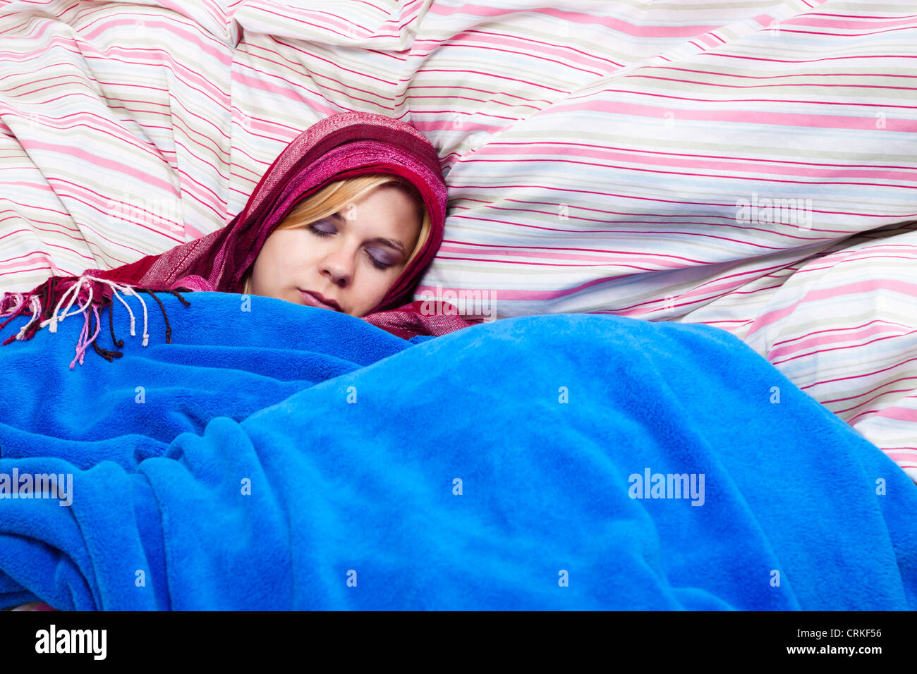 Young woman sleeping wrapped in a duvet. - Stock Image